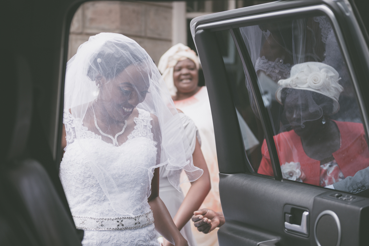 Joyous bride getting in the car ready for church