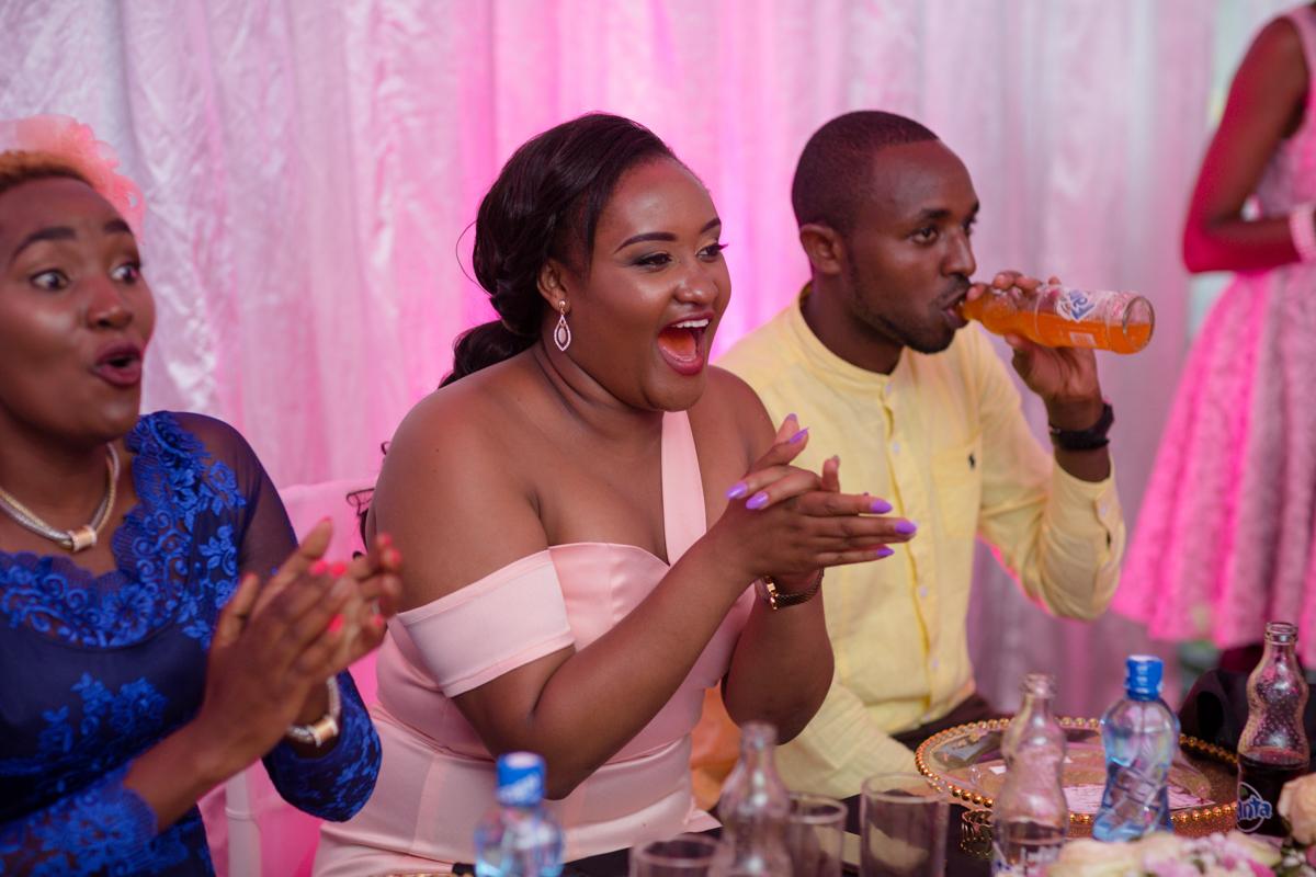 Bridesmaid enjoying the moment while Jeff Kuria the Mc drinks Fanta